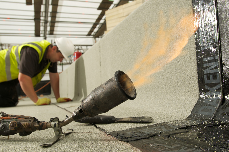 Someone installing a torch-on Bitumen system