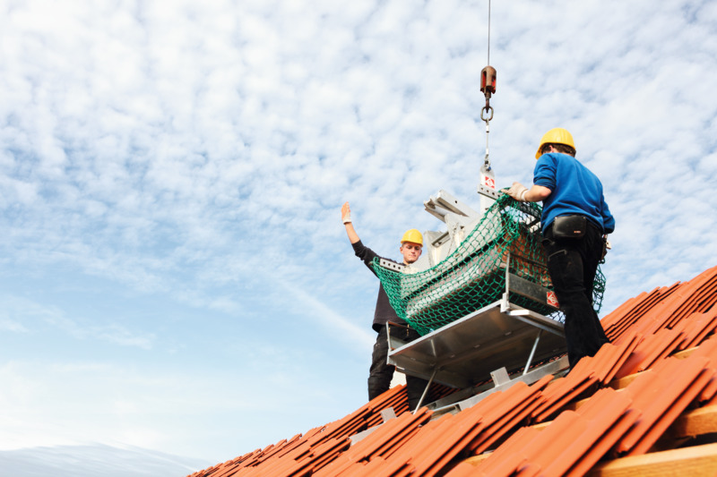 Roofers installing clay tiles