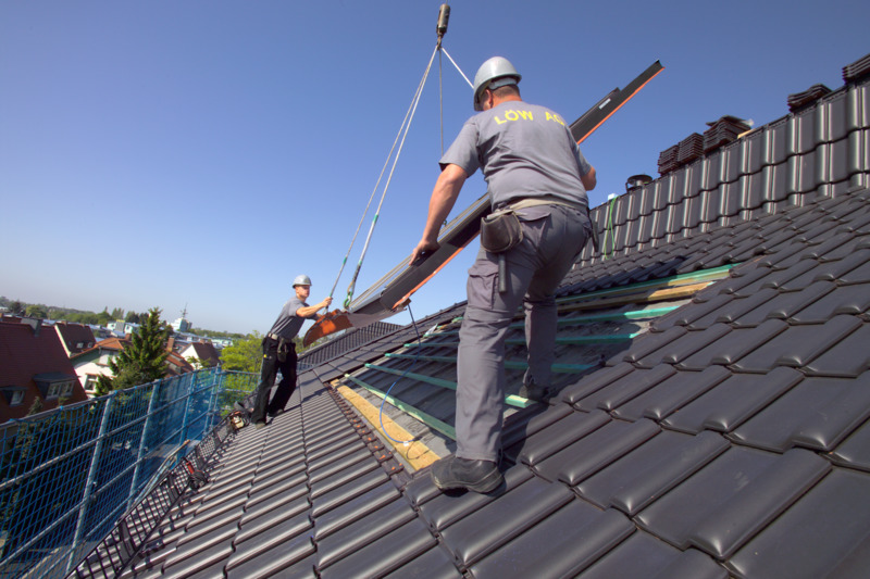 Roofers installing a PV panel on a pitched roof
