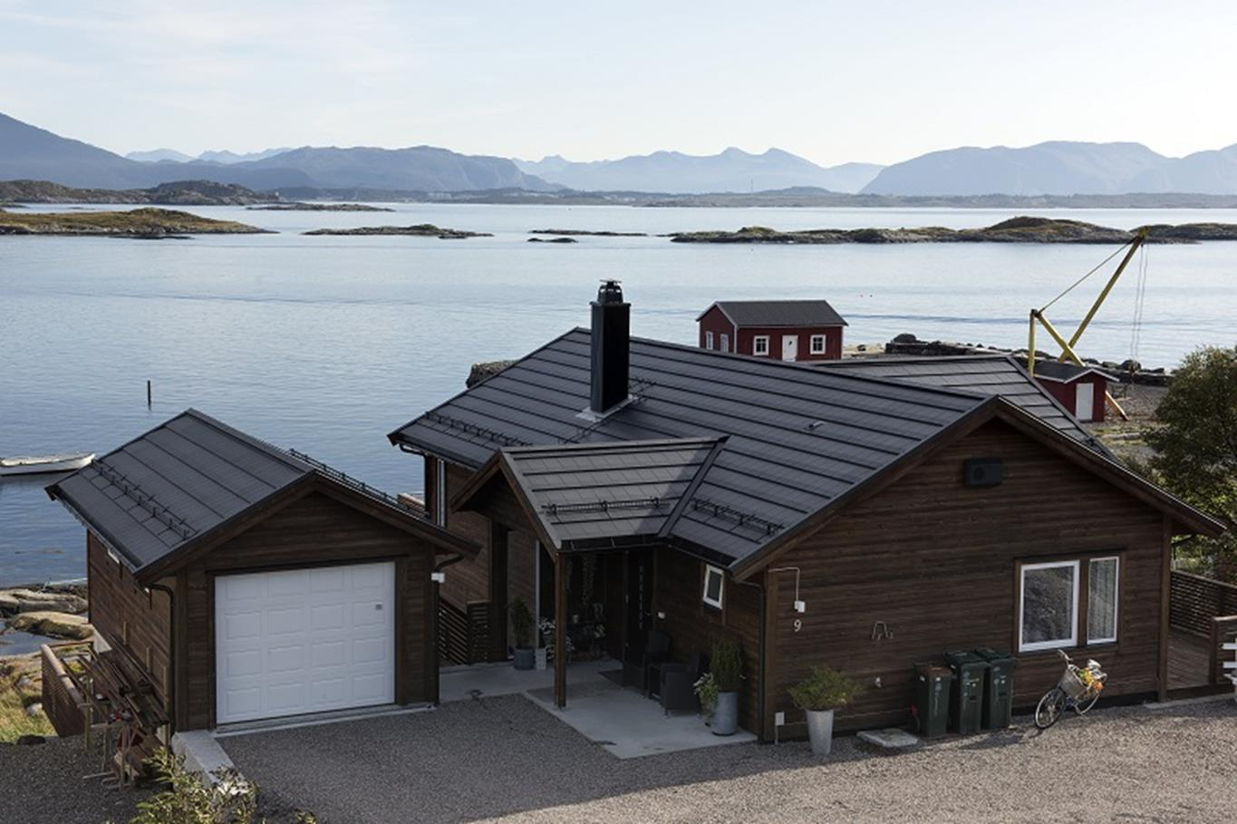 Pitched roof building with metal tile roof by tranquil water