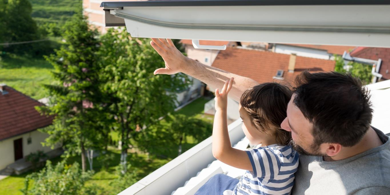 Father and child looking through roof window