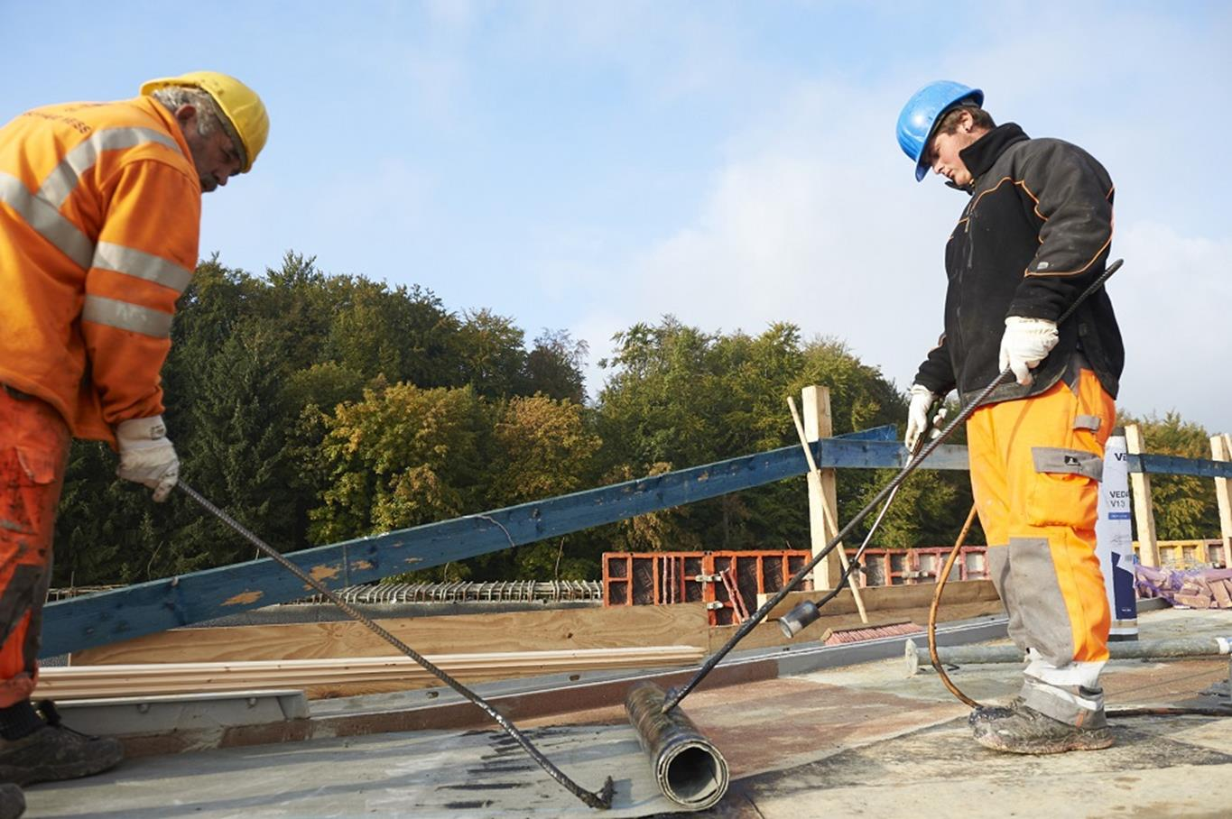 Two workmen working on a flat roof